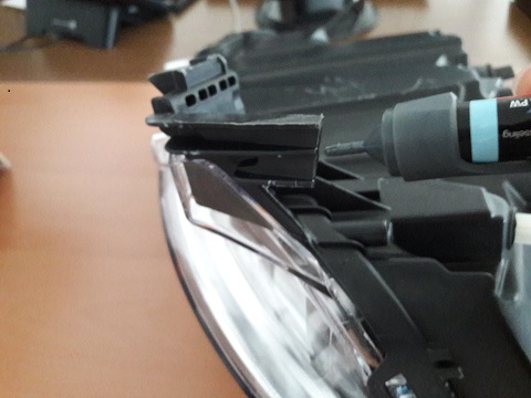 Anwendung des Blufixx Reparaturstiftes beim Ankleben einer Haltung von einem Autoscheinwerfer