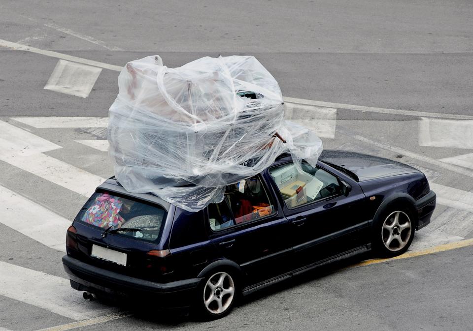 Vollgestopftes Auto mit Tüten, Kisten usw. Eingewickelte Möbel auf dem Dach. Als übertriebenes Bild für ein voll beladenes Auto zur Urlaubszeit