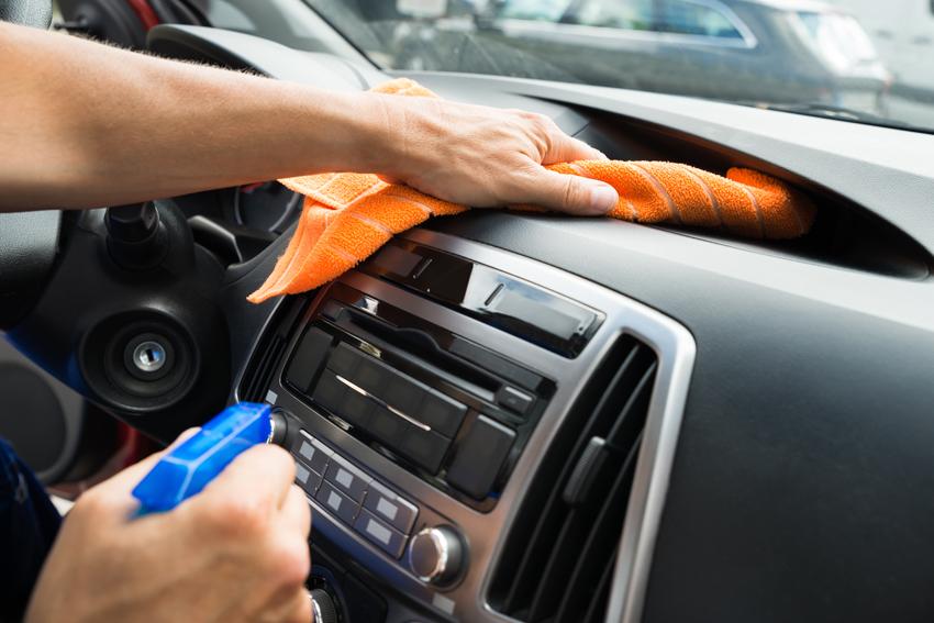 Person reinigt mit einem Lappen den Innenraum des Fahrzeugs und hält eine Sprühflasche mit passendem Reiniger in der Hand