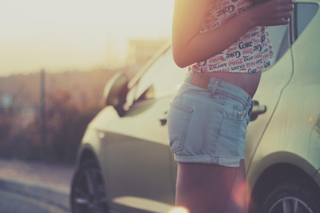 Frau in Shorts und bauchfreiem Top als Symbol für passende Bekleidung im Auto im Sommer