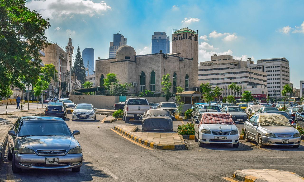 Parkplatz mit parkenden Autos im Schatten und abgedeckten Frontscheiben gegen Hitze im Auto