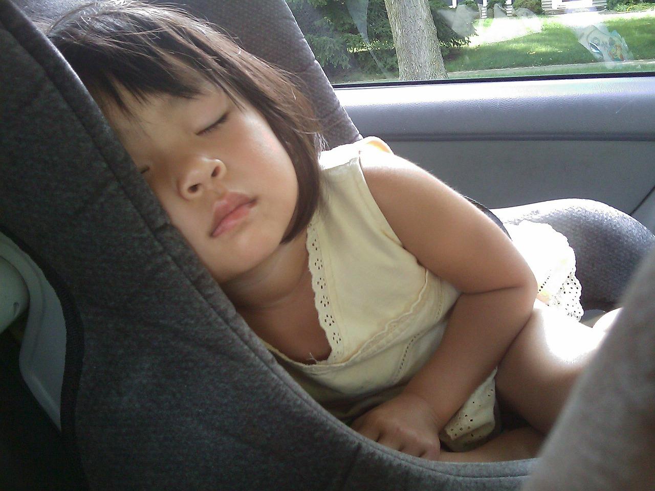 Schlafendes Mädchen im Kindersitz im Auto im Sommer