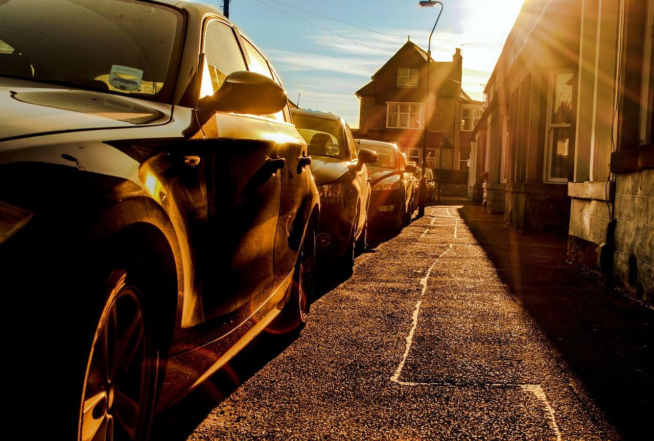 Parkende Autos auf der Straße in der flimmernden Sonne als Symbol für Hitze im Auto