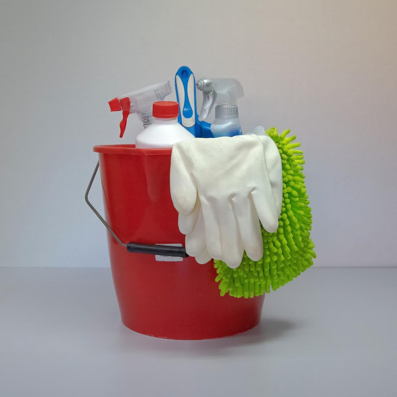 Eimer mit diversen Pflegeprodukten, Lappen und Handschuhen zur Autopflege