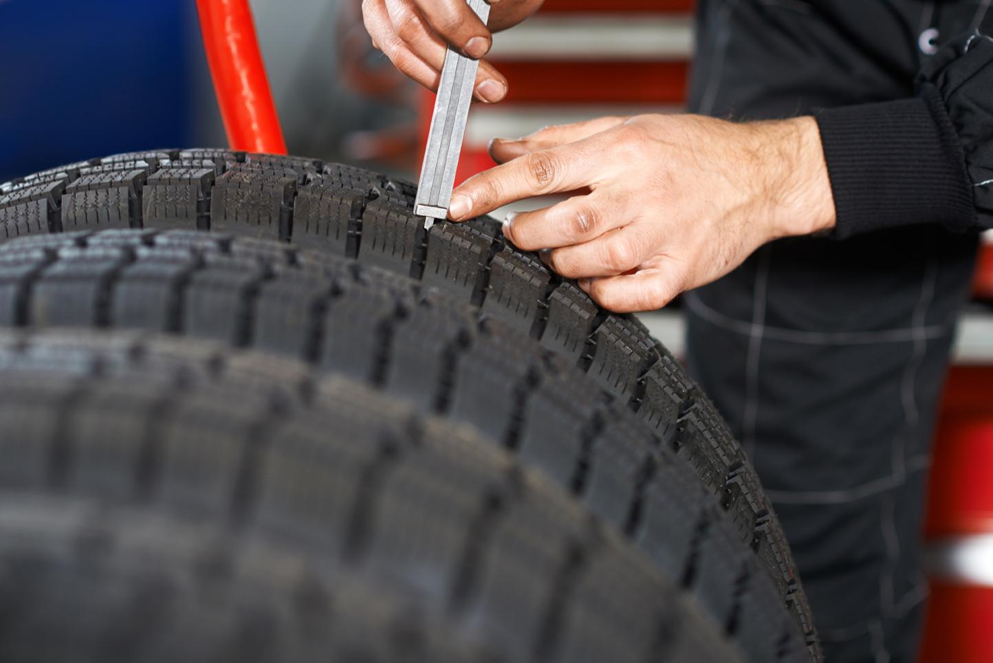 Reifen wird mit einem Profiltiefenmesser geprüft