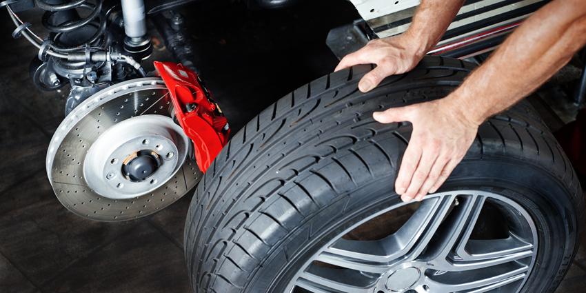 Aufgebocktes Auto, bei dem der Reifen schon abgenommen ist und auf dem Boden steht. Damit hat man einen guten Blick auf die Bremsanlage.