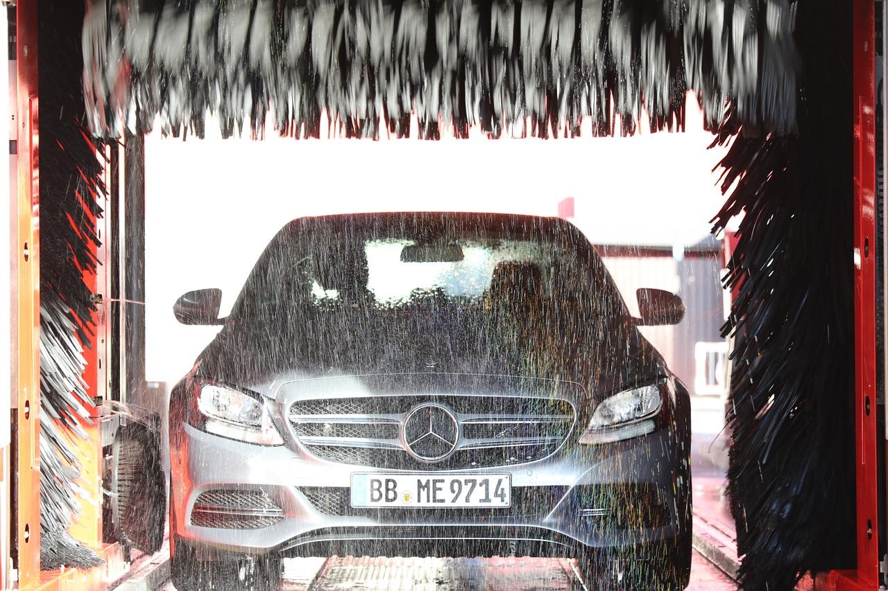 Fahrzeug in der Waschstraße von vorne zu sehen mit den Bürsten oben und an den Seiten
